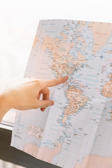 A person pointing finger toward the location on map