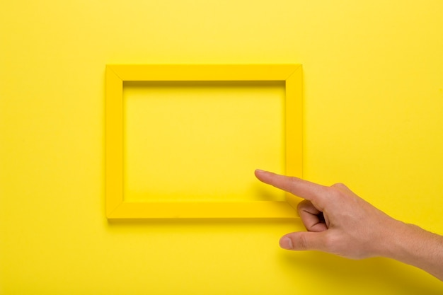 Person pointing to yellow empty frame