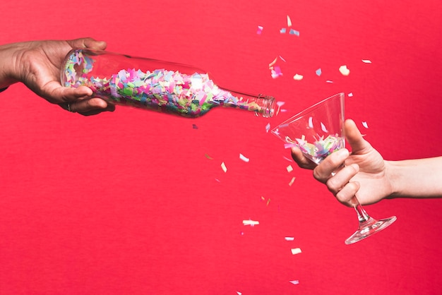 Coriandoli di versamento della persona dalla bottiglia al vetro su una priorità bassa rossa
