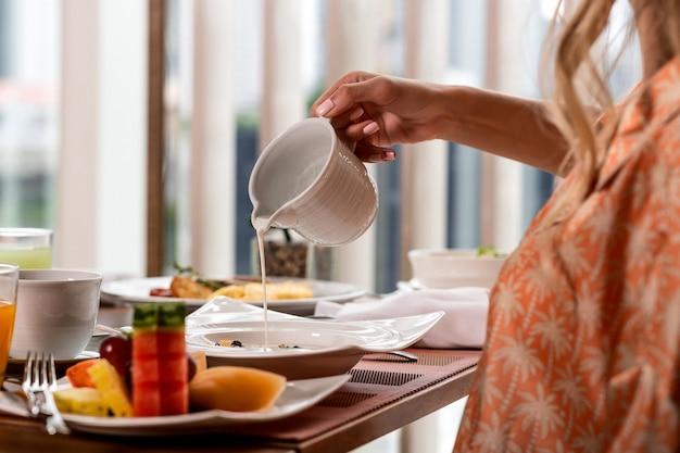 Человек наливает свежее молоко в миску с мюсли или мюсли