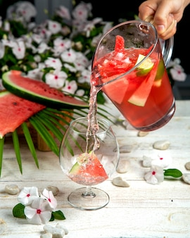 A person pouring homemade watermelon ice tea into a glass