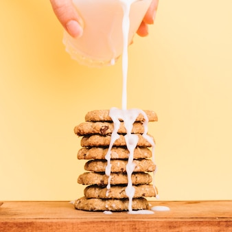 Person pouring milk from glass on cookies stack