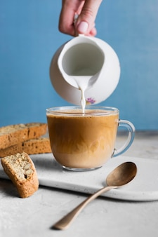 Person pouring milk in glass with coffee