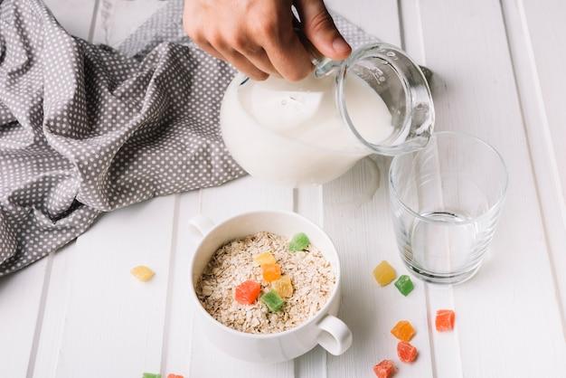 Una persona che versa il latte nel bicchiere con farina d'avena