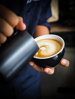 한 잔의 커피에 우유를 붓는 사람