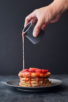 Person pouring strawberry sauce on a stack of pancakes
