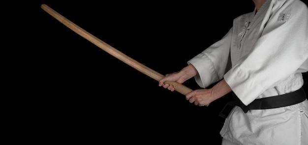 Человек практикует боевое искусство айкидо на черном фоне.