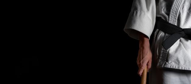 Человек, практикующий айкидо на черном фоне.