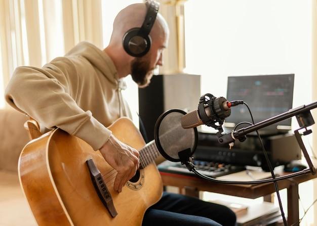 Человек, практикующий музыку в домашней студии