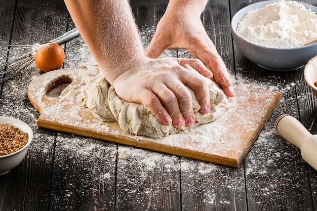A person preparing the bread dough on chopping board