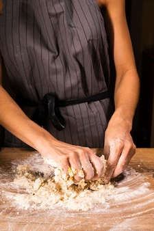 Person preparing dough with hands