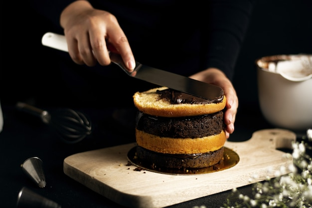 Person preparing a small cake with chocolate and vanilla layers