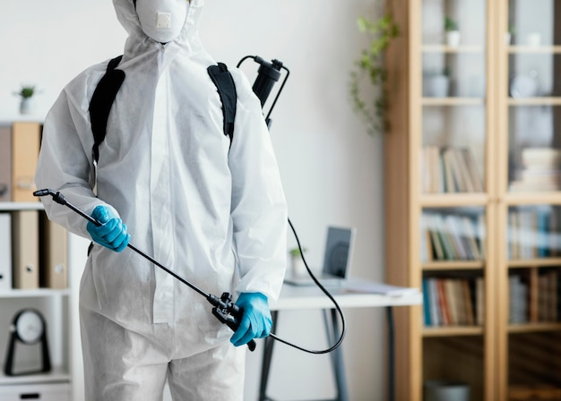 Person in protective equipment disinfecting Free Photo