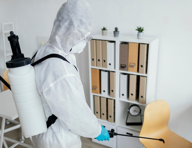 Person in protective equipment disinfecting