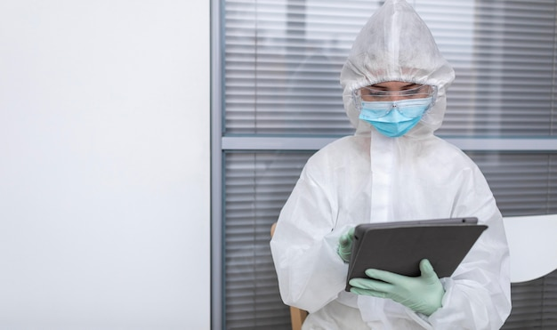 Person in protective suit looking at a tablet
