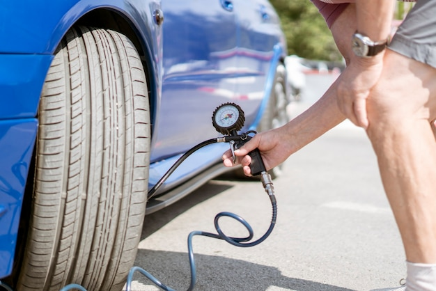 A person pump up the car wheels tires with a compressor with manometer