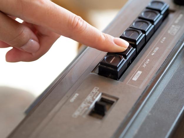 Человек нажимает кнопку музыкального проигрывателя