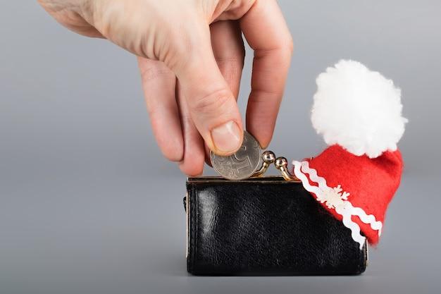 人は5つのロシアルーブルのコインを黒い革製の財布に入れます。閉じる
