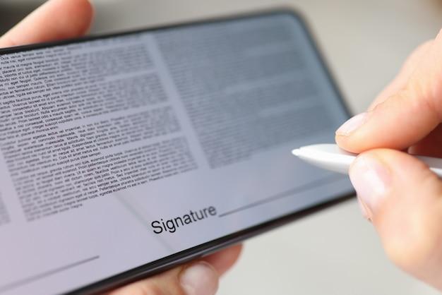 Человек ставит подпись стилусом на экране контракта смартфона