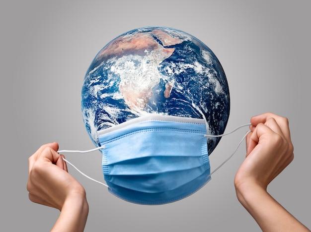 지구에 의료 마스크를 두는 사람