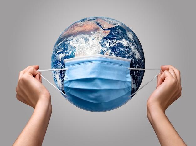 地球上に医療用マスクを置く人