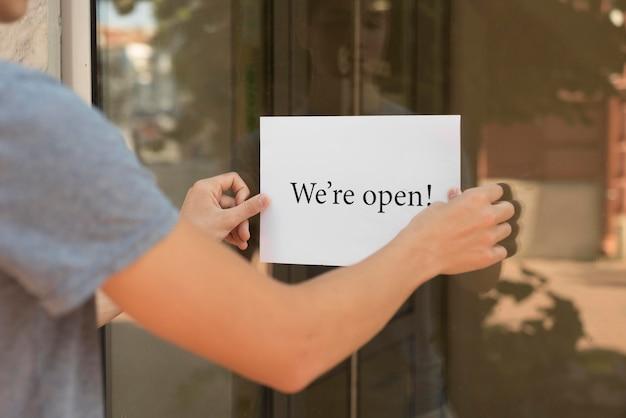 Человек, ставящий на дверь табличку «мы открыты»