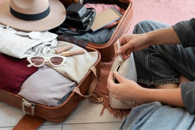 Человек кладет одежду в чемодан на отдых