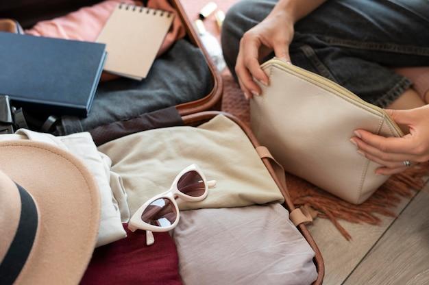Persona che mette i vestiti in una valigia per le sue vacanze