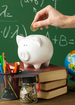 Person putting coins in piggy bank with books and academic cap