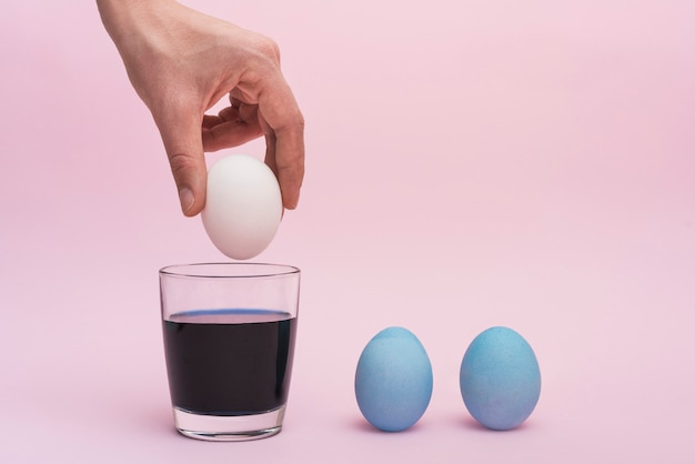 Person putting egg into glass with paint