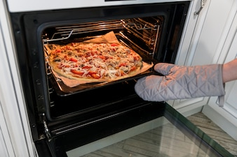 Person putting pizza in oven