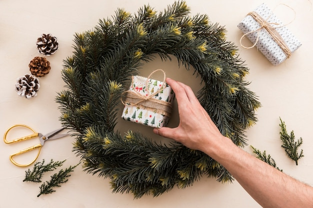 Person putting small gift box in christmas wreath