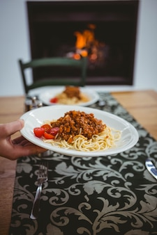 Person putting spaghetti on table at home