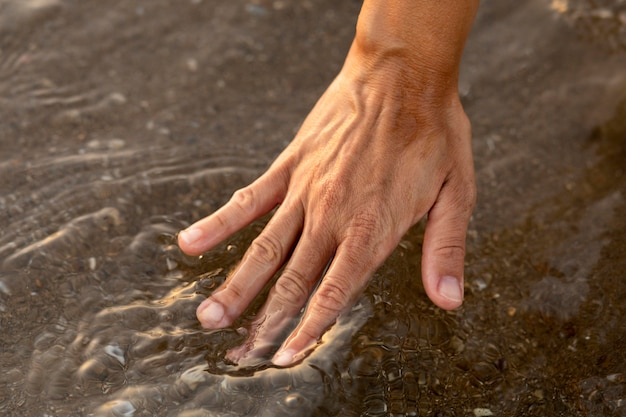 Person putting their hand in the water at the beach