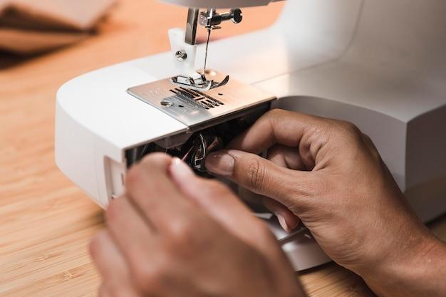 Человек, надевающий нитку на швейную машину