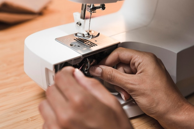 Person putting thread on a sewing machine