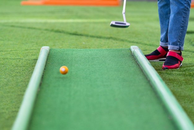 Person putting while playing a game of miniature golf