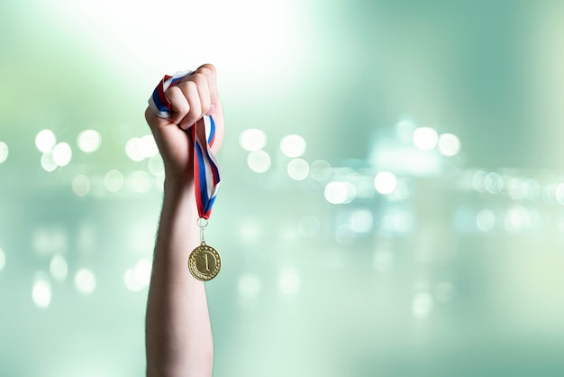 A person raised hand winning the first place, hand hold gold medal