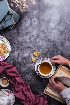 A person reading a book while taking a tea over a table with some coookies and a purple piece of fabric