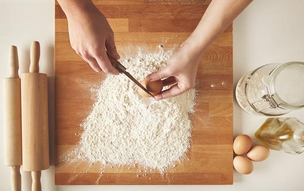 白い小麦粉の上に鶏の卵を割る準備ができている人