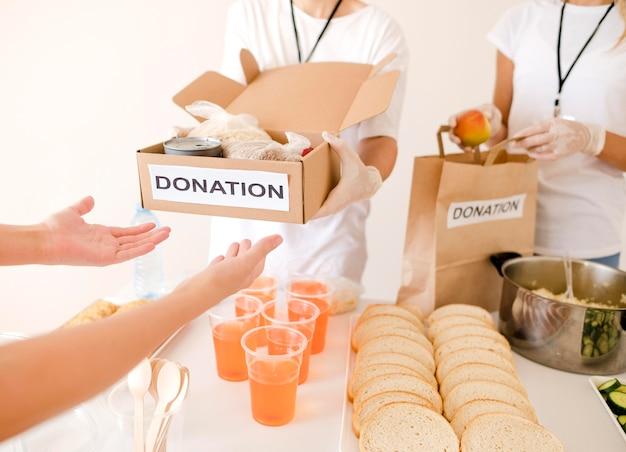 寄付された食品が入った箱を受け取る人