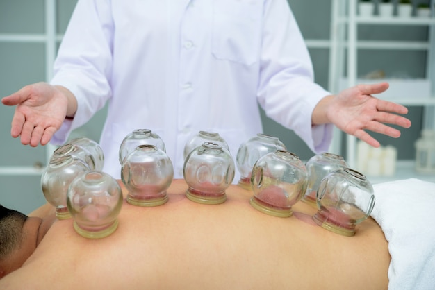 A person receiving cupping treatment on back in spa,traditional chinese medicine treatment.