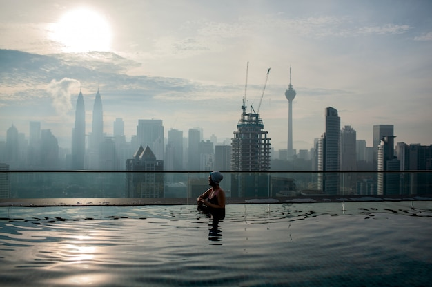 Person relaxing in pool and enjoying city panorama. kuala lumpur, malaysia