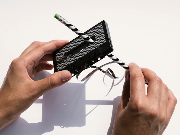 Person repairing black cassette tape with pencil