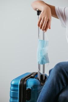 医療用マスクで荷物に腕を置いている人
