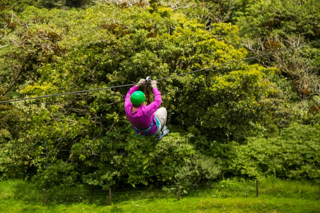 A person riding zip line over rainforest at costa rica