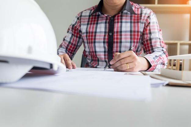 Инженер-физик план рисования рук на синем принтере или рабочий проект в его офисе с архитектурным оборудованием.