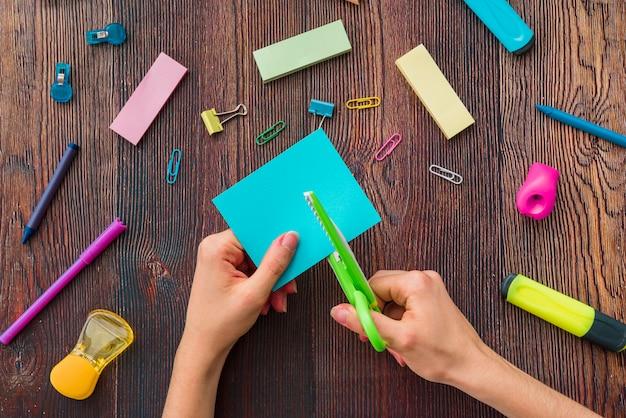 La mano della persona che taglia la carta blu sopra gli accessori della scuola sulla tavola di legno