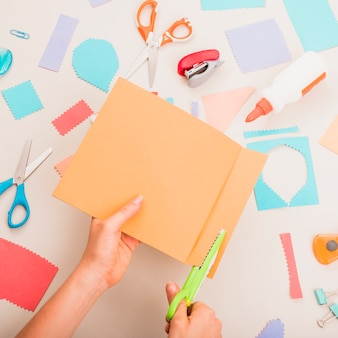 Person's hand cutting colorful paper over school supplies on table