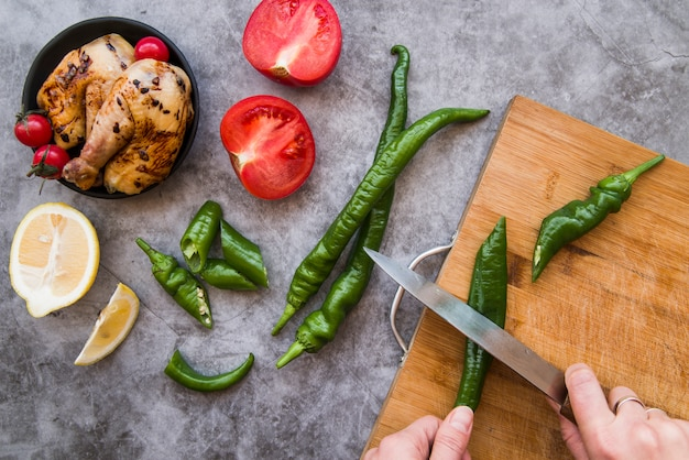 Person's hand cutting green chili on chopping board with roasted chicken and ingredients on concrete background